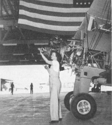 "Under the starts and stripes, Thunderbird II's maintenance crews ""keep' em flying"". This is Mrs. Evelyn Softly, who lists oiling props among other duties."