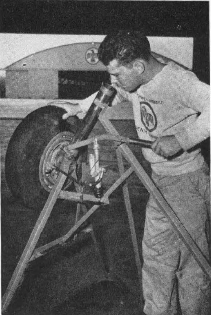 Time-saving, efficiency-improving devices a-plenty were invented by Southwest's maintenance departments. Glen Sweeten illustrates Thunderbird's latests at the time, for testing brake assemblies after they have been repaired but before they are mounted on landing gears. Previously, it was necessary to mount on the gear before testing the relined brake shoes or trued brake drums.