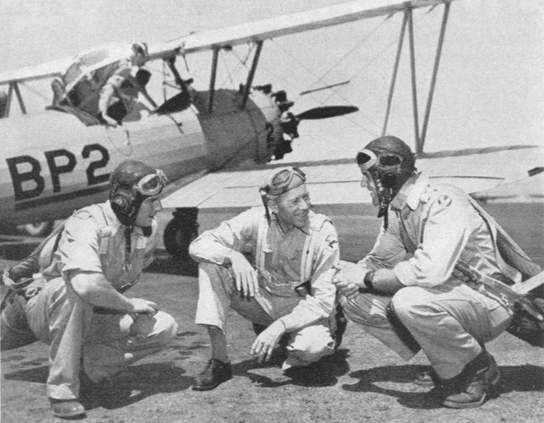 Smiling Jerry Bacon, Falcon flight commander (center), imparts confidence and flying instructions to air cadets who will finish the job he started in 1917. Here's a Falcon's World War I ace with an English and American cadet on the flight line.
