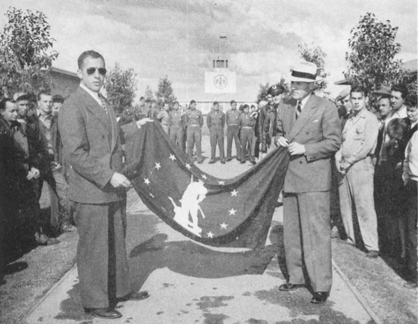 Field manager John Swope, receives Minute-Man flag from Walter R. Bimson , State chairman of the War Finance Committee. Fellow employees were proud of their subscription to War bonds.