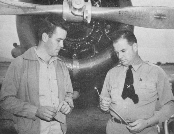 "Prize-winning gadget start pal nuts turning on engine cylinder base studs won $25 for James L. Thomas (left), the night repair foreman in the Thunderbird II Maintenance department, shown with Maintenance Superintendent Guy Polston, who is inspecting the device. It was hollow tube , about 16 inches long and with a slight bend at the operating end. A turning nut on one end rotates a speedometer cable in the core which, in turn , rotates gears on the operating end and the pal nut placed on its tip. Thomas, who was the first winner in the contest for ideas to improve maintenance work at both Thunderbird fields, said the inspiration for his gadget came to him during a ""brainstorm""."