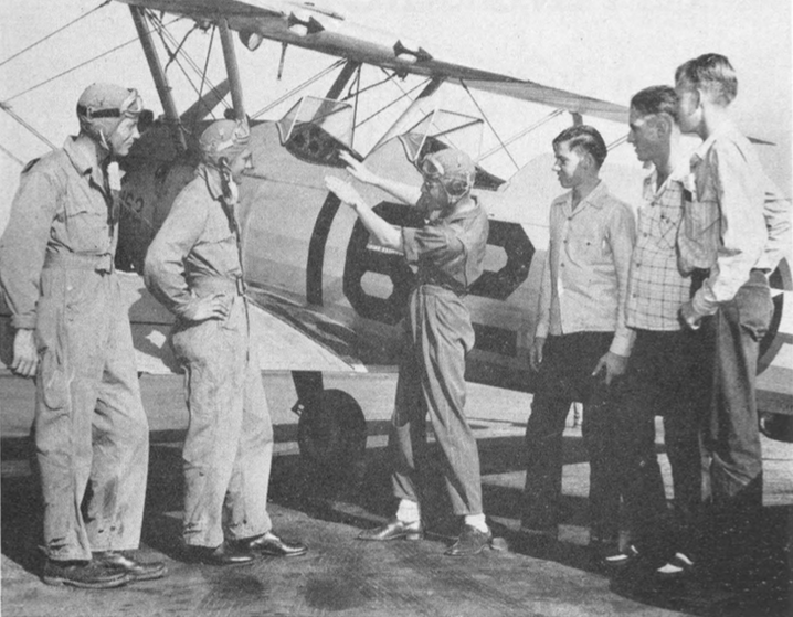 Airplane lore is being learned by high school boys  who are working both on the flight line and in the maintenance hangar at Thunderbird.  Picture shows Bill Daugherty , Elwood Evans and James Smithart , 17-year-old Glendale high school youths working on the flight line, listening as instructor Harold L. Bumph Jr. explains flight maneuvers to Aviation Cadet H. W. Hansen and W. E. Porter.